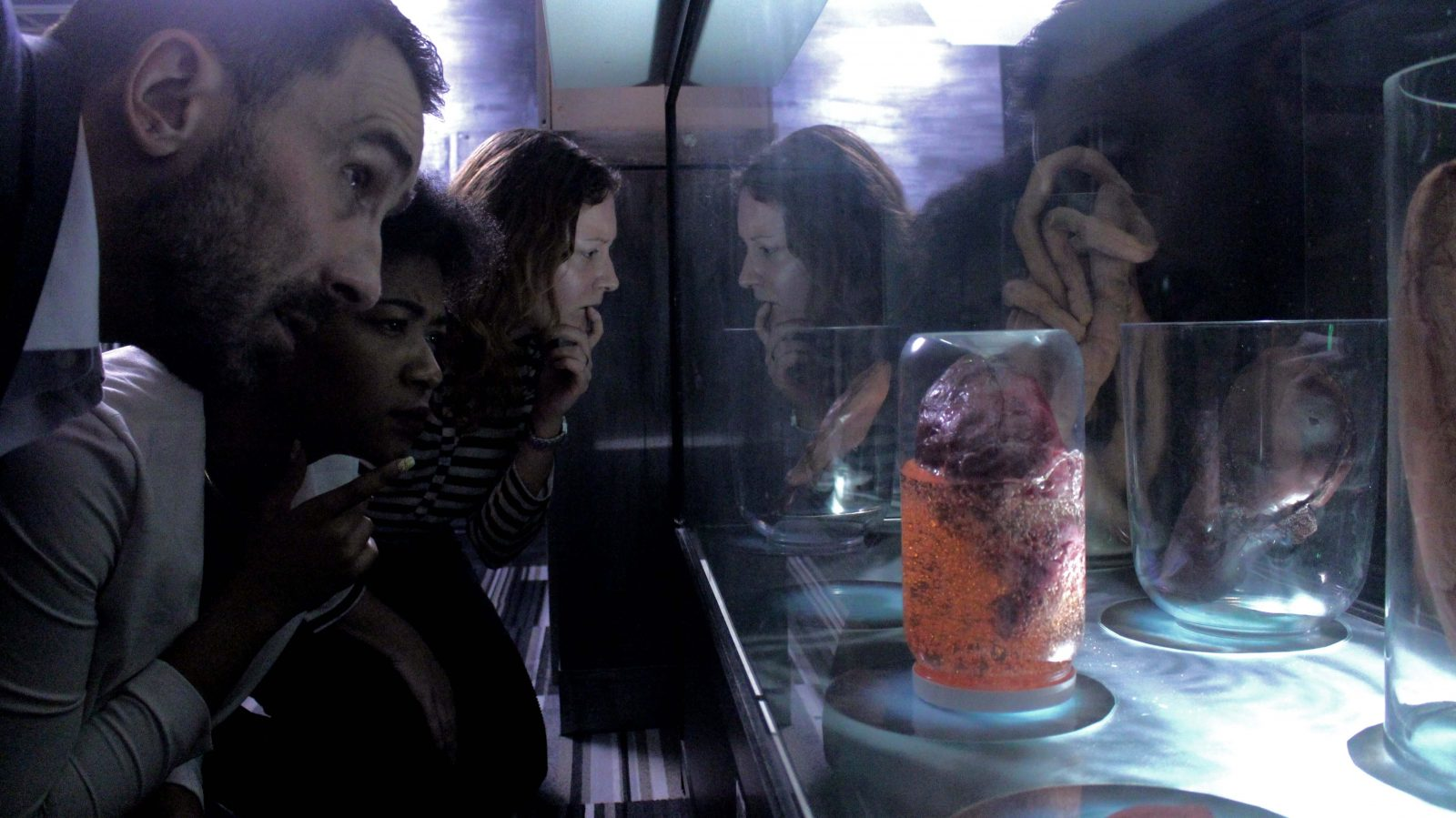 Three players in the alien encounter escape room looking closely at a container with a mysterious organ floating in goo.