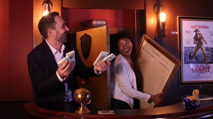 Two coworkers in the heist escape room, one is holding the declaration of independence, one is holding money. They're smiling at eachother.