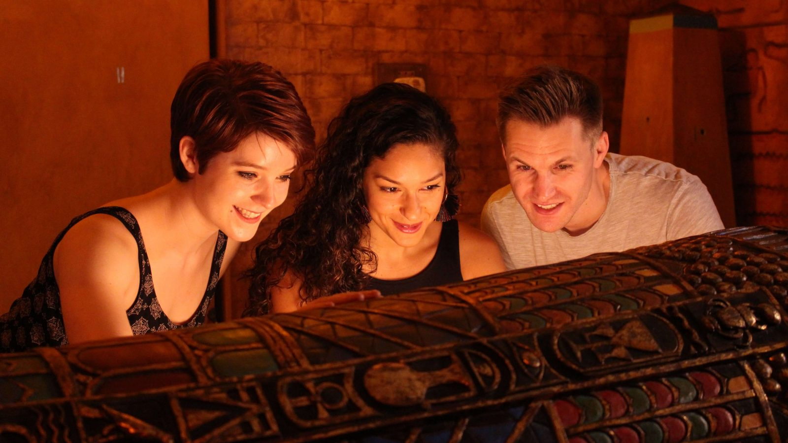 Three players in the egyptian tomb escape room looking down at a sarcophagus, their faces lit from below.
