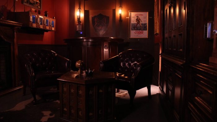 Clue Chase's heist escape room, red leather chairs are lit from behind by two old fashioned bulbs, there's a bar with dark wood and an old movie poster visible in the background.