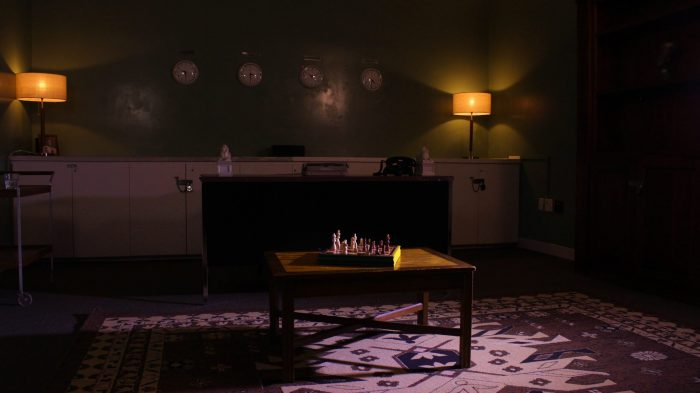 The lost spy escape room is shown, four clocks on the rear wall, a desk, an assembled chessboard are an typewriter are all visible.