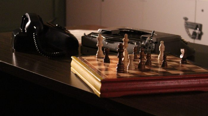 A closeup of a chessboard, typewriter and phone in the lost spy escape room
