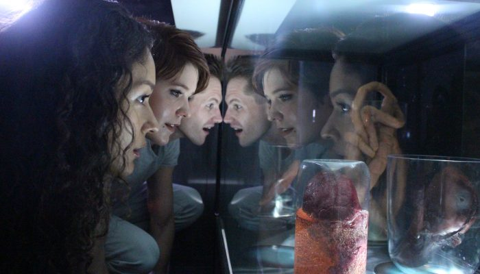 Three friends in the alien encounter escape room look into a mysterious glass container