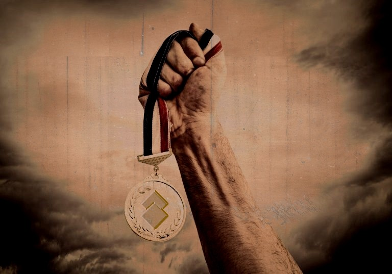 a hand holding up a medal with the artifact symbol on it