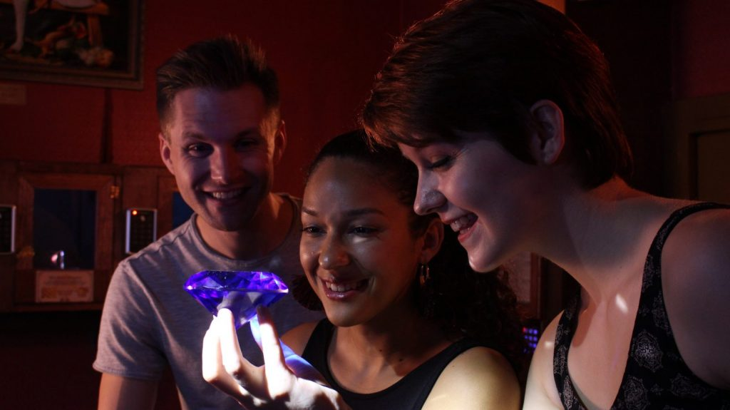 three players looking at a diamond from the heist escape